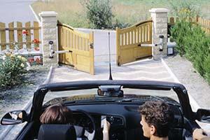 une voiture devant un portaille qui s'ouvre
